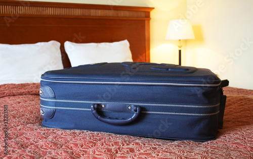 Suitcase on hotel bed