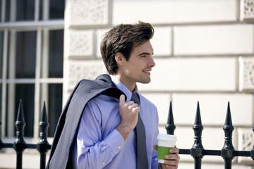 A businessman walking, holding a hot drink