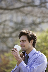A businessman drinking from a paper cup