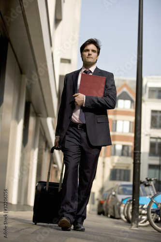 A businessman walking along the street, pulling his suitcase