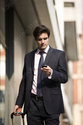 A businessman pulling a suitcase, using his mobile phone