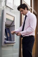 A businessman using a cash machine