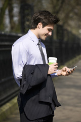 A businessman holding a hot drink, looking at his mobile phone