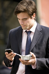 A businessman using his mobile phone, eating take-away food
