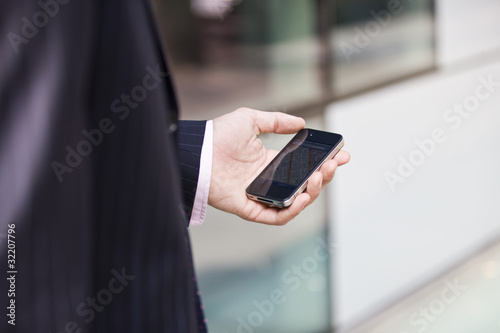 A businessman looking at a map on his mobile phone