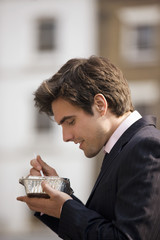 A businessman standing in the street, eating take-away food