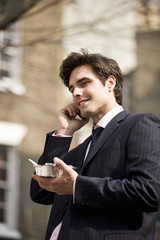A businessman talking on his mobile phone, eating take-away food