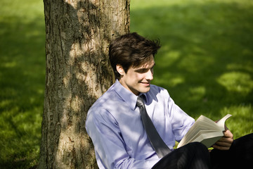 A businessman leaning against a tree, reading a book
