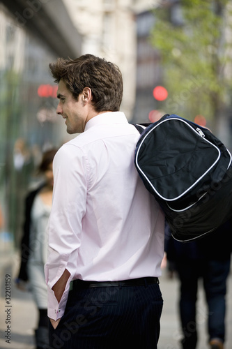 A businessman walking, carrying a gym bag