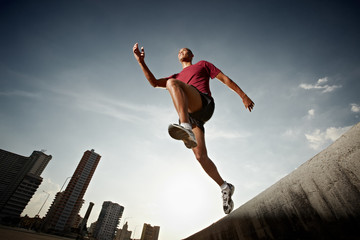 hispanic man running and jumping from a wall