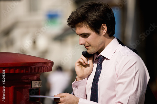 A businessman posting letters in a letterbox