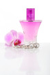 Diamond earrings, perfume and orchid flower
