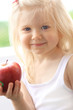 Beautiful smiling girl holding apple