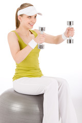 Fitness teenager woman with dumbbell sit on ball