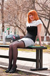Ginger-haired woman sitting on a bench