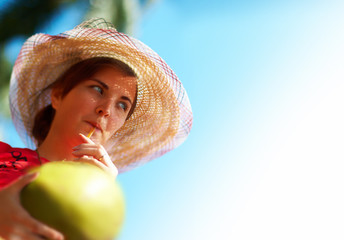 Beautiful woman drinking young and fresh coconut