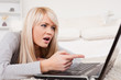 Pretty blond woman frustrated with her computer lying on a carpe