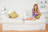 Attractive woman sitting on a sofa is going to make a payment on