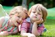 Zwei Kinder liegen auf dem Rasen