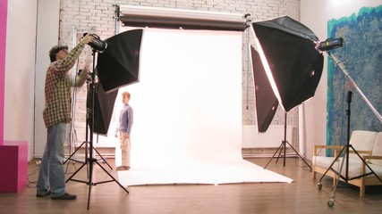 Photographer and kid adjust lightening at photo studio