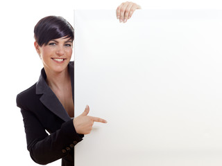 Beautiful woman pointing on a white blackboard with copyspace