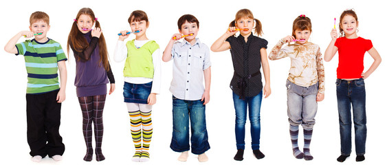 Several kids cleaning teeth or holding toothbrush in hand