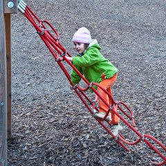 Preschool girl climbing in the playground