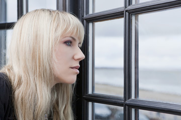 Attractive woman looking through the window
