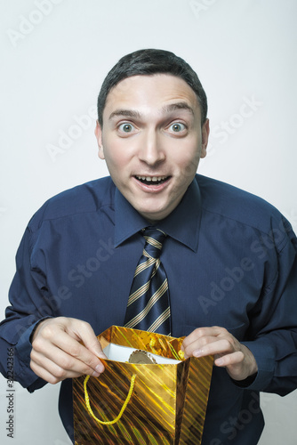 Surprised young man in tie opening packet with a present