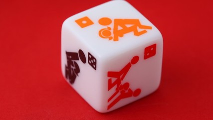 white dice with erotic icons on the sides, rotating on red
