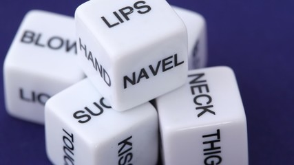 white dice with erotic messages on the sides, rotating on blue