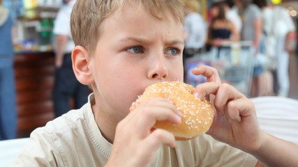 portrait of caucasian boy eating hamburger in cafe