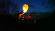man does some attempts to start chinese lantern, family look