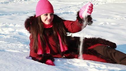 girl sitting in snow, takes his hand, throws up both hands
