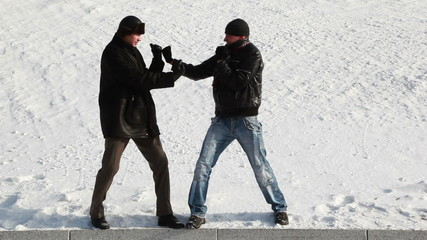 men snowy winter playfully imitating boxing match