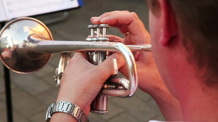 man playing trumpet march music sitting on sunny day