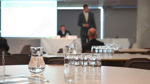Carafe with water and glasses in conference room
