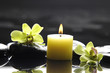 aromatherapy candle and zen stones with green orchid reflection