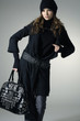 fashion model in autumn/winter clothes holding handbag posing