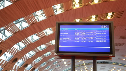 electronic information board under arched ceiling of airport
