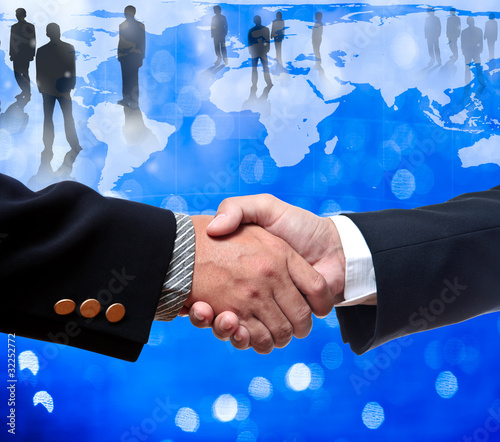 Shake hands with bussiness people standing on the globe