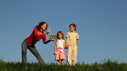 Boy and girl stand on grass, comes mother, click clapperboard