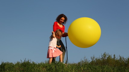 Woman with daughter stand on grass and blow up foot pump balloon