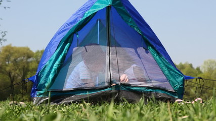 boy and girl close zipper mosquito net sitting inside tent