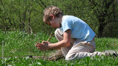 boy tries to take flame by primitive way with stick in wood