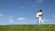 couple goes up grassy hill, holding hands and talking