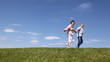 happy mature couple runs hand in hands by grass
