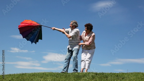 couple stands and pulls strongly curved umbrella by wind