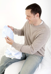 Man holding baby clothes