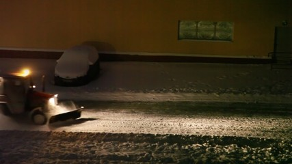 tractor cleans snow on street of city, move on read night